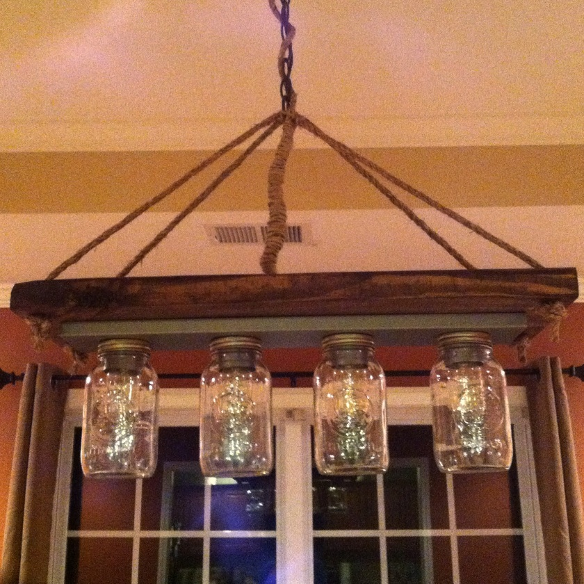 We made this chandelier from a vanity light strip and mason jars. We wired it into the existing light and it now hangs over our new table.